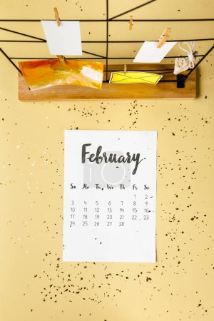 top view of february calendar with golden confetti and cards with clothespins on beige