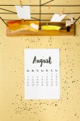 top view of august calendar with golden confetti and cards with clothespins on beige