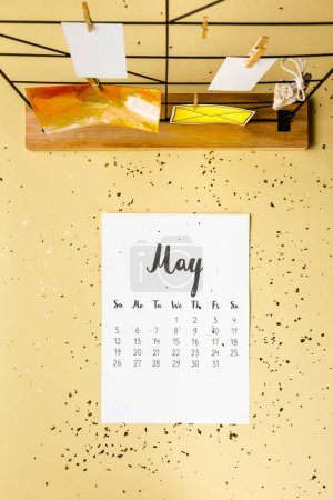 top view of may calendar with golden confetti and cards with clothespins on beige