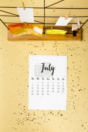 top view of july calendar with golden confetti and cards with clothespins on beige
