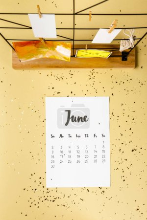 top view of june calendar with golden confetti and cards with clothespins on beige