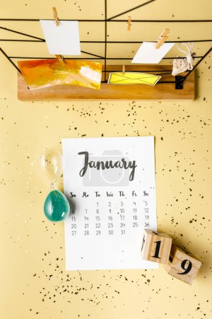 top view of january calendar with golden confetti and cards with clothespins on beige
