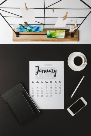 top view of january calendar with notebooks, smartphone and cup of coffee at workplace