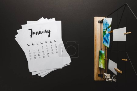 top view of january calendar and paintings on clothespins on black