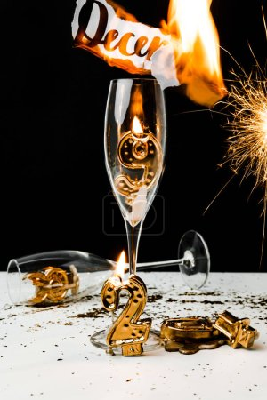 burning paper with december inscription, glasses, sparkler and 2019 numbers on black