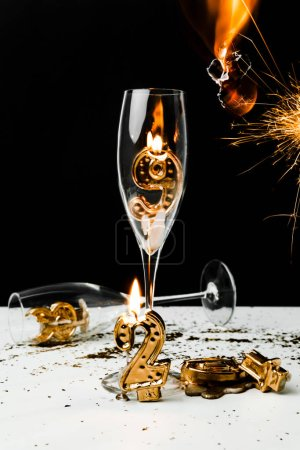 close-up view of champagne glasses with candle, sparkler and golden 2019 numbers on black