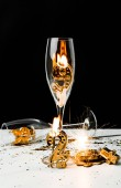 champagne glasses with candle, sparkler and golden 2019 numbers on black