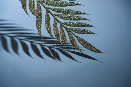 close up view of festive branch decorated by golden glitter and shadow, christmas background concept