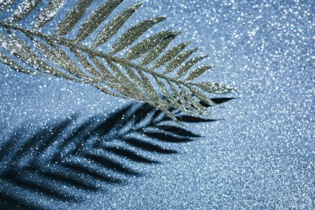 branch decorated by golden glitter and shadow on sparkling surface, christmas background concept
