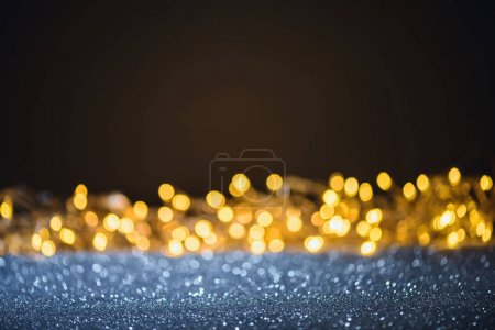 selective focus of blurred sparkling lights and bokeh on black