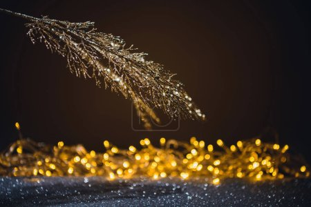 festive branch decorated by golden glitter and shadow, christmas background concept