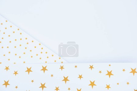 top view of festive paper decorated by golden stars isolated on white