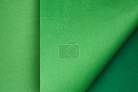 top view of green paper on colored background