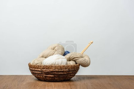 close up view of yarn with knitting needles in wicker basket on wooden tabletop on grey background
