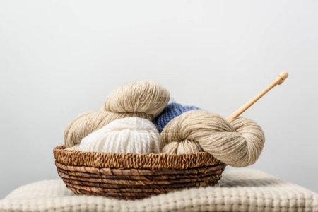 Foto de Cerrar vista de hilo con agujas de tejer de cesta de mimbre en gris telón de fondo - Imagen libre de derechos