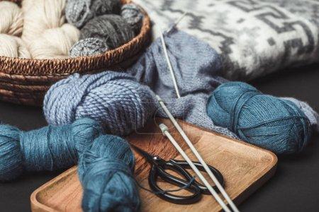 Foto de Cerrar vista de punto, tijeras y agujas de tejer en oscurezca mesa con manta - Imagen libre de derechos