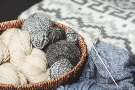 close up view of knitting clews in wicker basket with grey blanket on background