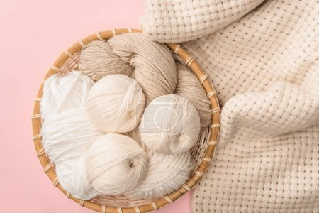 top view of yarn in wicker basket on pink background with knitted blanket