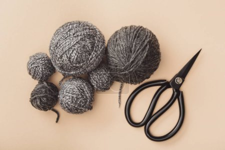 flat lay with grey knitting and scissors on beige backdrop
