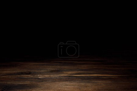 Photo for Dark brown striped wooden tabletop on black - Royalty Free Image