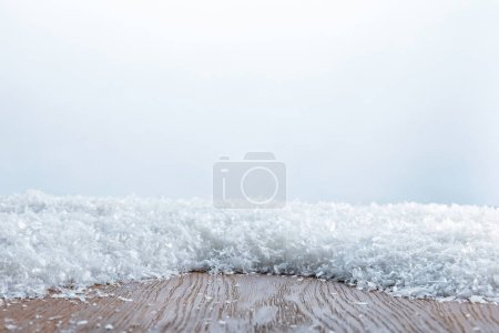 brown striped textured board covered with snow on white