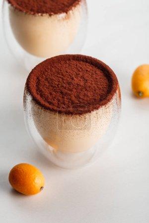 Tiramisu-Desserts mit Kakaopulver in Gläsern auf grauem Tisch mit Kumquats