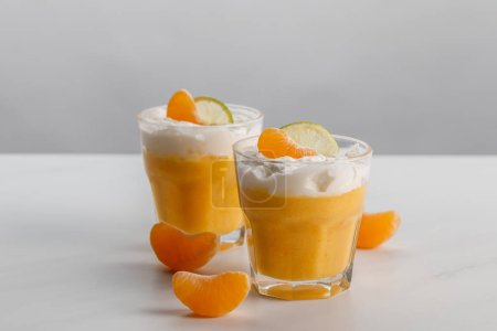 Photo for Two glasses with cream desserts with tangerine and lime slices - Royalty Free Image