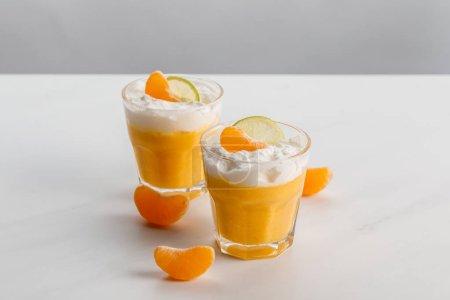 Photo pour Verres avec des desserts orange avec des tranches de mandarine et de citron vert - image libre de droit