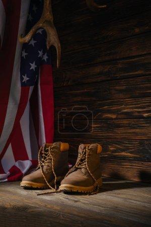 Photo pour Chaussures de randonnée, de cornes et de drapeau américain sur une surface en bois, concept de voyage - image libre de droit