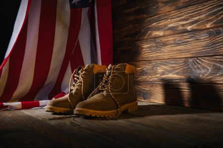 Photo for Trekking boots and american flag on wooden surface, travel concept - Royalty Free Image