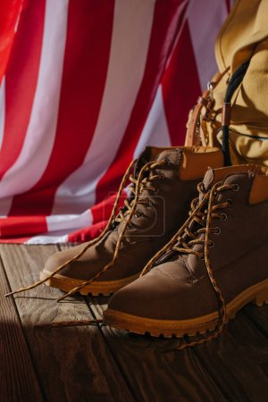 close-up view of trekking boots, backpack and american flag on wooden surface