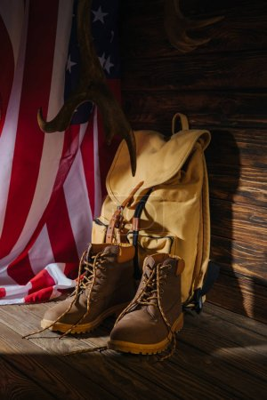 Photo for Trekking boots, backpack, horns and american flag on wooden surface - Royalty Free Image