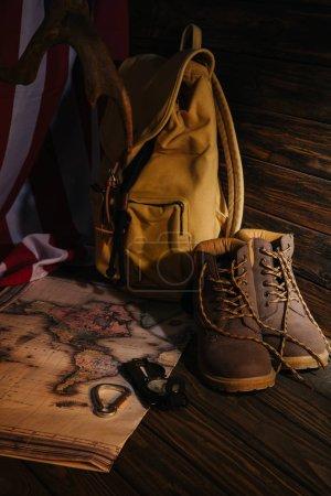 Foto de Vista cercana de botas de trekking, excursiones de equipo, mapa, mochila y bandera americana sobre superficie de madera - Imagen libre de derechos