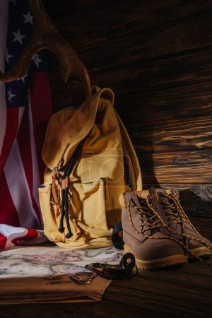 close-up view of trekking boots, hiking equipment, map, backpack and american flag, travel concept