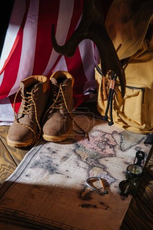 trekking boots, map, compass, backpack and american flag on wooden surface