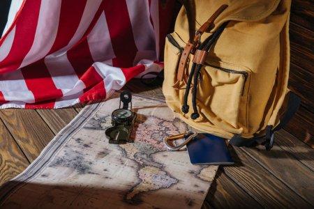 Photo pour Sac à dos, boussole, passeport, carte et drapeau américain sur la surface en bois - image libre de droit