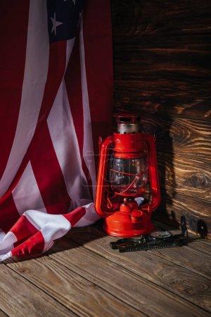 Photo pour Vue rapprochée du drapeau américain, de la lanterne rouge et de la boussole sur la surface en bois - image libre de droit