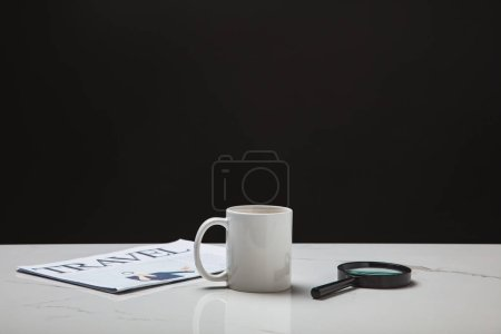 close-up view of cup, magnifying glass and travel newspaper on white surface on black