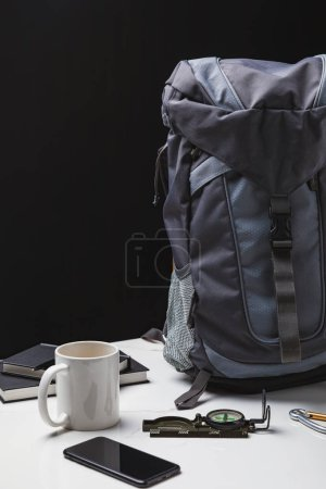 backpack, smartphone, cup and compass on black, travel concept