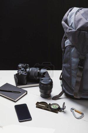 Photo pour Sac à dos, smartphone, appareil photo avec objectif et suivi des équipements - image libre de droit