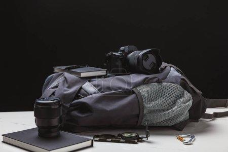 Photo pour Sac à dos, appareil photo et matériel de trekking sur noir - image libre de droit