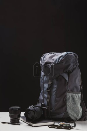 Photo for Backpack, photo camera with lens, notebook and trekking equipment on black - Royalty Free Image