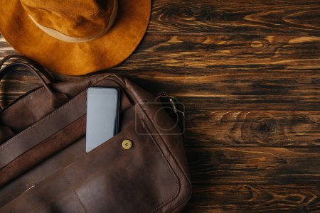 Photo for Top view of brown leather bag with smartphone and hat on wooden table, travel concept - Royalty Free Image