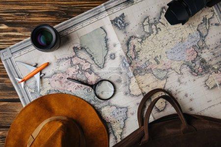 Photo pour Vue du dessus du sac en cuir brun, chapeau, loupe, petit avion modèle, appareil photo et objectif sur la carte - image libre de droit