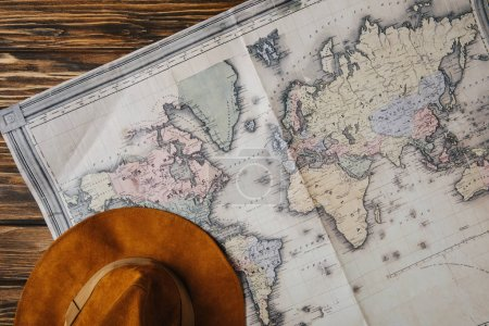 top view of brown hat and map on wooden table, travel concept