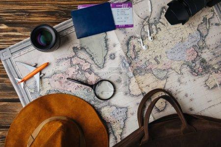 vue du dessus de sac en cuir brun, chapeau, loupe, petit avion modèle, écouteurs, appareil photo, objectif et passeport avec carte d'embarquement sur la carte