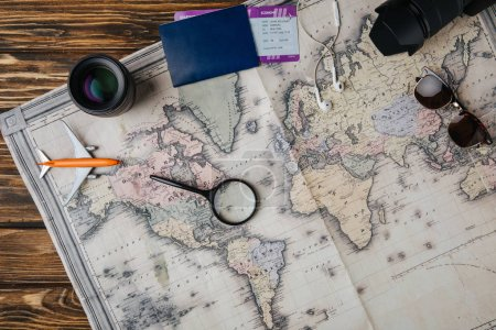 top view of magnifying glass, small model plane, sunglasses, photo camera, lens and passport with boarding pass on map