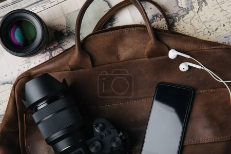 top view of brown leather bag with photo camera, lens, smartphone and earphones on map