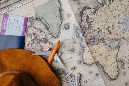 Photo pour Vue du dessus du passeport avec carte d'embarquement, chapeau, écouteurs et petit avion modèle dans la carte - image libre de droit