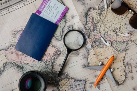 Photo for Top view of passport with boarding pass, lens, magnifying glass, earphones, sunglasses and small plane model on map - Royalty Free Image